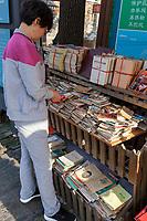 Yangzhou, Jiangsu, China.  Customer Looking at Used Books, Dong Guan Street.