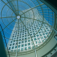 View up through the glass dome of a neighbouring building to one of several skycrapers which dominate the skyline of London's Canary Wharf