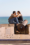 Spanish couple kissing on ledge in Sitges, Spain