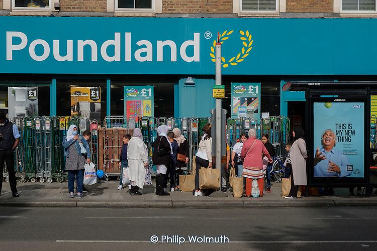 Bus stop queue outside a Poundland store, Kilburn, London.