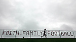 An Aplington-Parkersburg football player runs laps along a fenceline bearing a message before the team's practice.