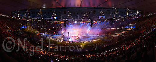 """27 JUL 2012 - LONDON, GBR - Four orange rings move across the  stadium as the fifth ring begins to rise during the """"Pandemonium"""" section of the Opening Ceremony of the London 2012 Olympic Games in the Olympic Stadium in the Olympic Park, Stratford, London, Great Britain (PHOTO (C) 2012 NIGEL FARROW)"""