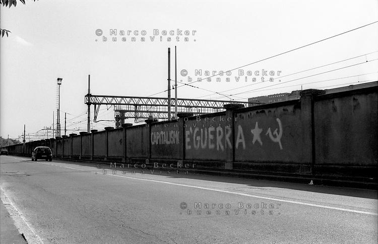 """Milano, periferia nord. Scritta """"capitalismo è guerra"""" sul muro dello scalo merci ferroviario greco - breda --- Milan, north periphery. """"Capitalism is war"""" written on the wall of disused freight railway yard of greco - breda"""