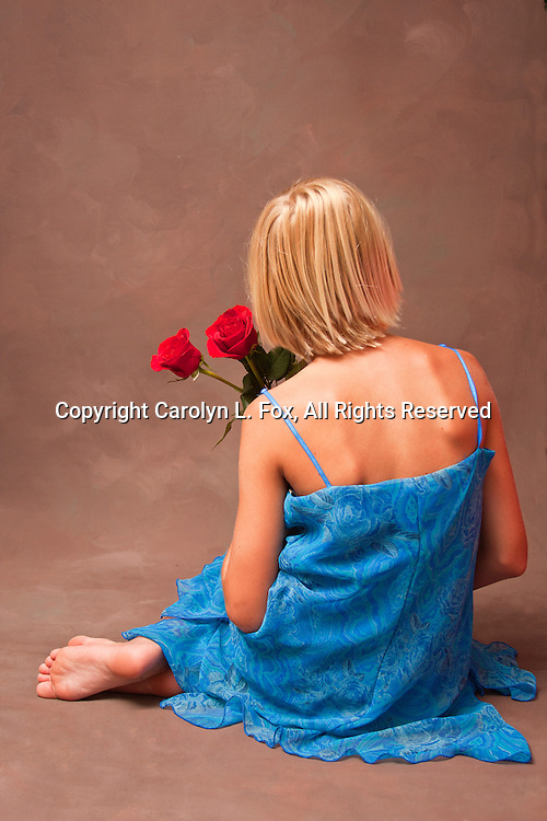 A young woman holds beautiful red roses.  She's wearing a pretty blue dress.