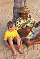 Local island man teaching young visitor boy the ukulele