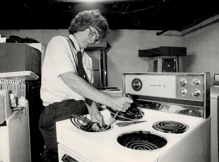 1987 FILE PHOTO - ARCHIVES -<br /> <br /> Barbara Elend fixes a stove at Karl's Appliance Service. The 44-year-old mother of three was a teacher and then a homemaker before she decided to enter the appliance repair trade.<br /> <br /> 1987<br /> <br /> PHOTO :  Erin Comb - Toronto Star Archives - AQP
