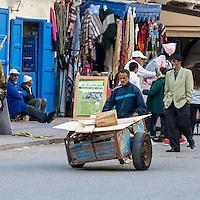Essaouira, Morocco.  Porter Pushing Cart, Avenue de l'Istiqlal.