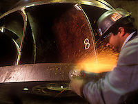 Worker grinds surface of hydroelectric turbine during maintenance