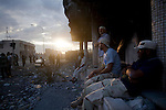 Revolutionary fighters sat near the front line on Dubai Street, where pro-Gaddafi snipers took up positions, in central Sirte, Libya, Oct. 13, 2011. Revolutionary forces solidified control of the pro-Gaddafi stronghold, but fighting continued in a few neighborhoods.