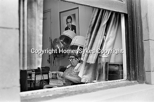 Woman reading newspaper in beauty parlour hair dryer Manhattan, New York. 1969, USA 60s