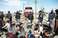 Pictured: Migrants sit on the railway track with riot police on stand by Thursday 03 March 2016<br /> Re: Migrants have closed off the railway track at the Greek Fyro Macedonian border in Idomeni, Greece,