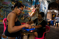 An Afro-Colombian street beautician gives a manicure to a market vendor in the market of Bazurto in Cartagena, Colombia, 12 December 2017. Far from the touristy places in the walled city, a colorful, vibrant labyrinth of Cartagena's biggest open-air market sprawls to the Caribbean seashore. Here, in the dark and narrow alleys, full of scrappy stalls selling fruit, vegetables and herbs, meat and raw fish, with smelly garbage on the floor and loud reggaeton music in the air, the African roots of Colombia are manifested.
