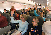 Passengers signal their answers to a flight attendant's question about ticket prices minutes before the inaugural flight of Skybus Airlines from its  Columbus, Ohio, hub Tuesday, May 22, 2005.  Skybus Airlines Inc., will compete with Southwest Airlines Co., JetBlue Airways Corp. and other low-cost companies.