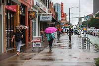 Students and pedestrians walking on a rainy day on the Drag next to the University of Texas campus in Austin, Texas - Stock Image.