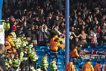 """Portsmouth 1 Southampton 1, 18/12/2012. Fratton Park, Championship. Stewards trying to restrain vising Southampton fans as they react with delight as their team take the lead during the second half of their Championship fixture against Portsmouth at Fratton Park stadium. Around 3000 away fans were taken directly to the game in a fleet of buses in a police operation known as the """"coach bubble"""" to avoid the possibility of disorder between rival fans. The match ended in a one-all draw watched by a near capacity crowd of 19,879. Photo by Colin McPherson."""