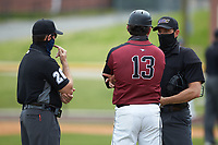 Home plate umpire Jerry Buresh (right) listens as North Carolina Central Eagles head coach Jim Koerner (13) argues a call during the game against the North Carolina A&T Aggies at Durham Athletic Park on April 10, 2021 in Durham, North Carolina. (Brian Westerholt/Four Seam Images)