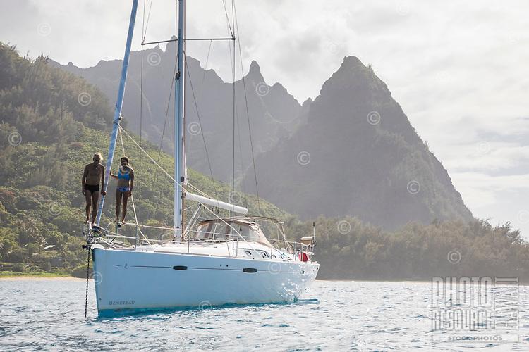 A couple stand on the bow of an anchored sailboat on the Na Pali Coast of Kaua'i.