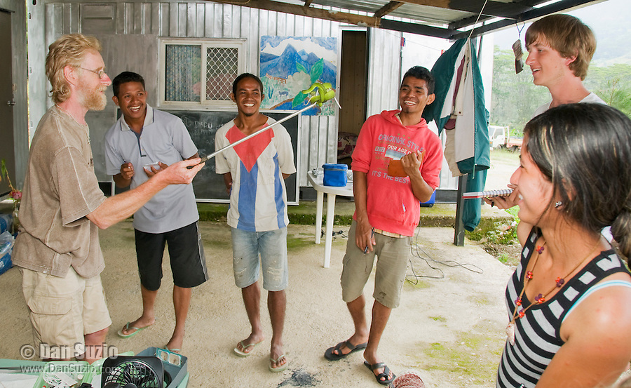 British herpetologist Mark O'Shea holds a Sunda Island pitviper, Cryptelytrops insularis. Looking on are Timorese students Benny Carvalho, Laca Ribeira, and Zito Soares, and American students Eric Leatham and Marianna Tucci. Bakhita Mission, near Eraulo, Ermera District, Timor-Leste (East Timor)