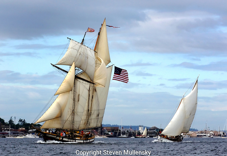 Two schooners race under full sail on Port Townsend Bay during the Northwest Schooner Regatta. The schooners are sailing by the town of Port Townsend, Washington, the first established city in the state, dating from 1852. The annual event attracts schooners from throughout the northwest and Canada.