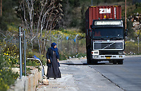 Pictured: A migrant woman walks alone on the main road near the refugee camp Tuesday 23 February 2016<br /> Re: Migrants at a refugee camp in the Schisto area of Athens, Greece.