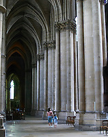 The Reims Cathedral: a woman and child walking along one of the aisles looking up admiring and awed by the gothic arched vaults, Reims, Champagne, Marne, Ardennes, France, low light grainy grain