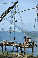 Fishermen hauling Chinese-style nets, Kochi, Kerala, India.