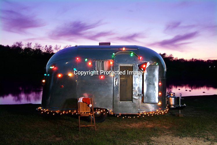 An Airstream Pacer decorated with Christmas lights and Santa hats sitting next to a lake.