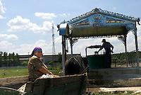 REPUBLIC OF MOLDOVA, Gagauzia, Comrat, 2009/07/3..On leaving Comrat among brownfields, peasants come to fetch water from the well. Each fountain is sanctified, an icon representing the patron saint is placed on the side of the well..© Bruno Cogez / Est&Ost Photography..République Moldave, Gagaouzie, Comrat, 3/07/2009..A la sortie de Comrat, parmi les friches industrielles, des paysans viennent chercher de l'eau au puits. Chaque fontaine est sanctifiée : une icône représentant le saint protecteur est placée sur le côté du puits..© Bruno Cogez / Est&Ost Photography