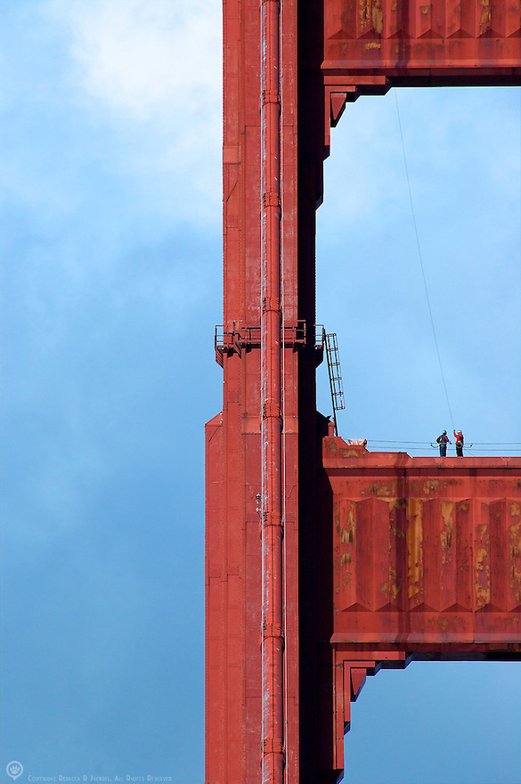 Two workers converse on the top of one of the towers on the Golden Gate Bridge in San Francisco, California