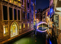 Reflected neon light onto bridge over canal in Venice, Italy