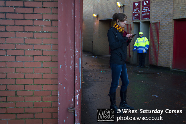 Motherwell 3 Dundee 1, 12/12/2015. Fir Park, Scottish Premiership. A woman supporter with a mobile phone outside the Davie Cooper Stand at Fir Park, home to Motherwell Football Club, before they played Dundee in a Scottish Premiership fixture. Formed in 1886, the  home side has played at Fir Park since 1895. Motherwell won the match by three goals to one, watched by a crowd of 3512 spectators. Photo by Colin McPherson.