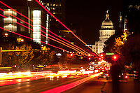 Cars and busses whizzing past downtown Austin with the illuminated Texas State Capitol as backdrop.