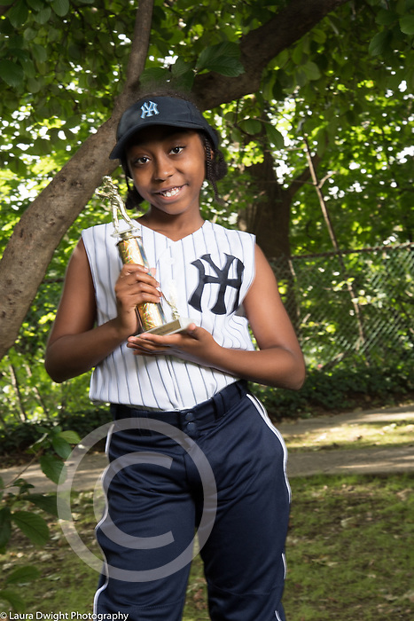 10 year old girl in summer softball outfit holding trophy she is proud of