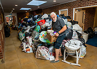 BNPS.co.uk (01202 558833)<br /> Pic: MaxWillcock/BNPS<br /> <br /> Pictured: Volunteer Brian Platt, 69, sorting the pile of donations.<br /> <br /> A flood of donations for Afghan refugees has inundated a church which has been left with a 24ft long stack of parcels.<br /> <br /> Ross Donaldson posted on a Facebook community group asking if anyone had clothes to offer, sparking an overwhelming response from his community.<br /> <br /> After organising to keep donations at Immanuel Church, Bournemouth, Dorset, he arrived the next morning to find a pile of bags.