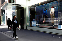 NEW YORK, NEW YORK - MARCH 12: A woman crosses a Burberry store on March 12, 2021 in New York. Burberry expects full-year profits to beat market forecasts after a rebound in sales in the fourth quarter, sending its shares more than 6% higher. (Photo by Emaz/VIEWpress)