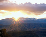 Sun setting behind the La Sal Mountains with slickrock formations, from Island in the Sky area, Canyonlands National Park, Moab, Utah, USA.