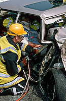 Firefighter using a  hydraulic ram to prize open the door of a crashed car invoved in a road traffic accident. The driver is still trapped and paramedics are placing a plastic collar around her neck, to ensure that it remains stable, whilst she is being extricated...© SHOUT. THIS PICTURE MUST ONLY BE USED TO ILLUSTRATE THE EMERGENCY SERVICES IN A POSITIVE MANNER. CONTACT JOHN CALLAN. Exact date unknown.john@shoutpictures.com.www.shoutpictures.com...