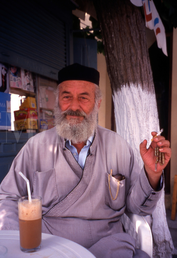 Greece. Crete. Episkopi Village Priest, sat with his Frappe