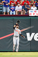 Baltimore Orioles outfielder Nick Markakis #21 makes a catch during the Major League Baseball game against the Texas Rangers on August 21st, 2012 at the Rangers Ballpark in Arlington, Texas. The Orioles defeated the Rangers 5-3. (Andrew Woolley/Four Seam Images).