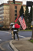 USA, Oregon, Veterans dressed in camouflage crossing the street carrying American Flag in Portland