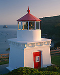 Humbolt County, CA:  Trinidad Memorial Lighthouse stands above small boats harbored in Trinidad Bay
