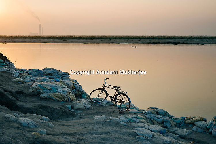 A bicycle stand on the Ganges bank covered up with sand filled gunny bags these prevents the river from eating away the main road to Hossainpur, Kulidihar. Murshidabad District, West Bengal, India.