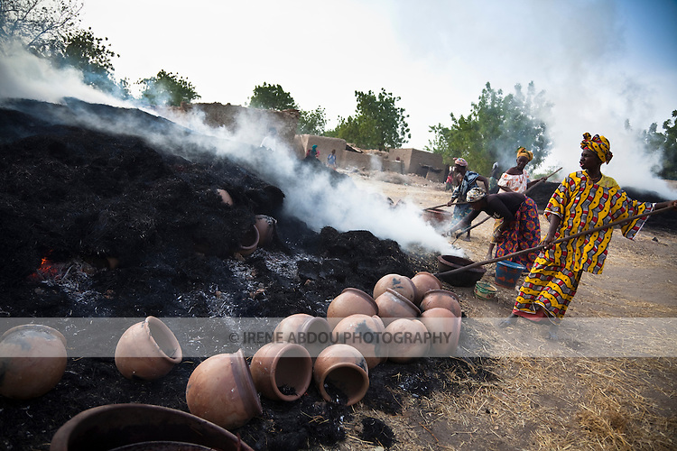 In the village of Kalabougou near Segou, Mali, women of the numu blacksmiths population have worked for centuries as traditional potters.  A 7-day fabrication cycle leads to the weekly Saturday afternoon firing of the kilns, in which large stacks of pots are covered with grass and set on fire.  Here, women remove their pots from the simmering stacks using hooks attached to the ends of long wood poles.  The pots are immediately dipped into a water-berry mixture that hardens it and gives a reddish color.