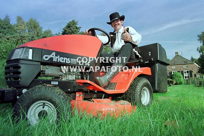 Archieffoto van Bennie Jolink tijdens het grasmaaien in zijn tuin.Op de achtergrond zijn huis.<br /><br />Foto voor PRIVE pagina