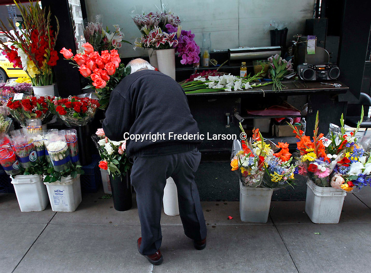 A man arranges flowers at a stand near Union Square in San Francisco, California.