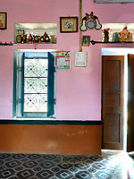 A niche above the shuttered window in the bedroom displays a collection of school trophies awarded to the children of the family