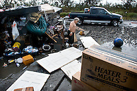 Hilton Chaisson empties the contents of his flooded house into the yard for rubbish pick up. His home flooded after hurricane Gustav delivered wide spread wind damage and water damage to the predominantly Native American community of Isle Jean Charles, Louisiana. The family home has been flooded by storm water nearly a dozen times since it was built.