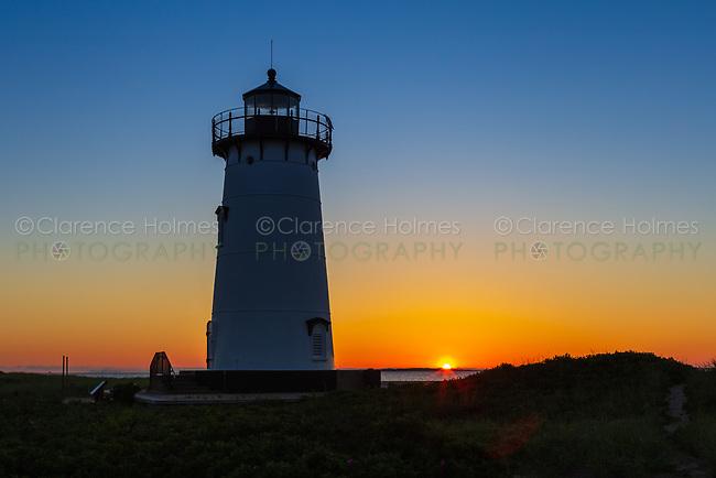 The rising sun adds color to the sky behind Edgartown Harbor Light in Edgartown, Massachusetts on Martha's Vineyard.