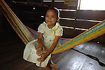 Smiling girl in dress on hammock in her home in Midway village in southern Belize