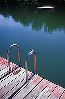 Ladder on pier with reflections of trees on lake<br />